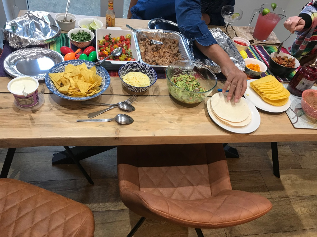 Mexican food served across a dinner table, a hand already grabbing the first tortilla.