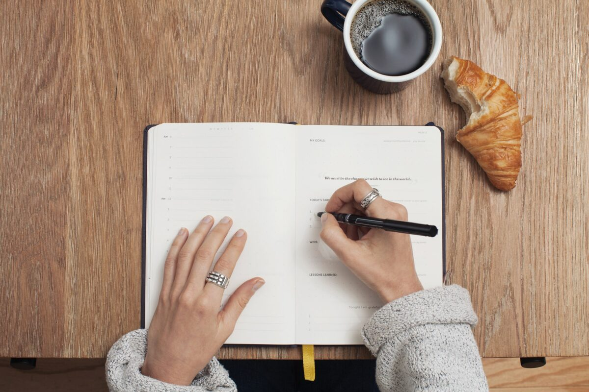 In this image, someone is writing on a notepad, a croissant and a hot drink in a mug is sitting to the side of the notepad.