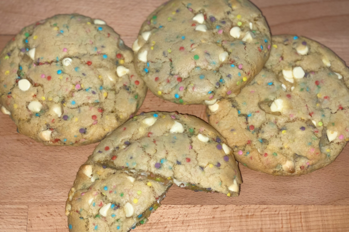 This image shows four funfetti cookies as the central focus. They have been placed onto a wooden block.