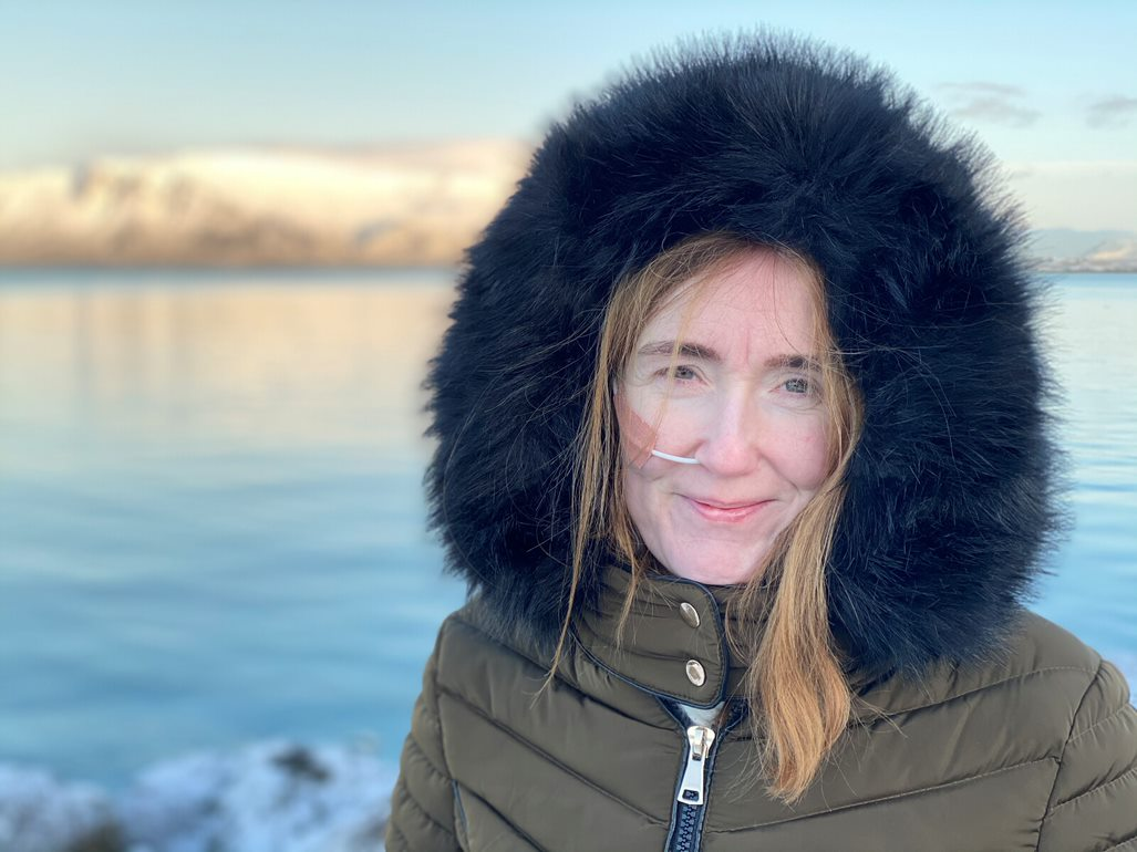 Louise stands in the foreground of this picture with a green jacket with a large black hood. She smiles in the picture and we can see her feeding tube. In the background is the landscape of Iceland, with a beautiful reflective lake.