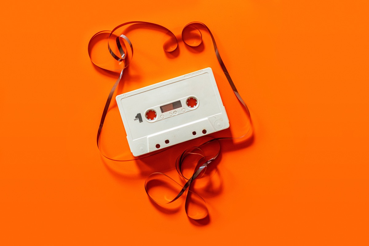 An unravelled cassette tape on an orange background.