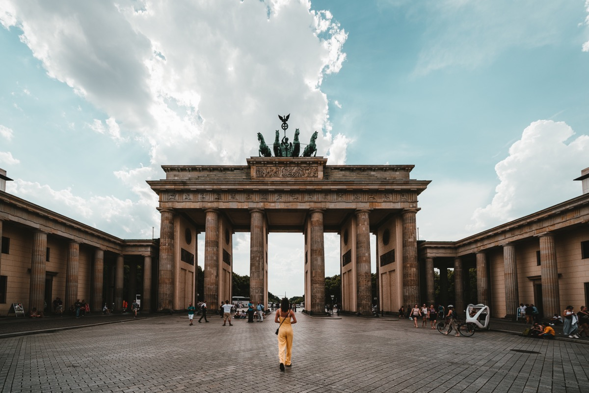 This is an image of some architecture in Berlin. The main focal point is of the huge building. It has six columns with a slab across the top. The sky is blue but cloudy in the background. There is a lady dressed in yellow in the foreground.