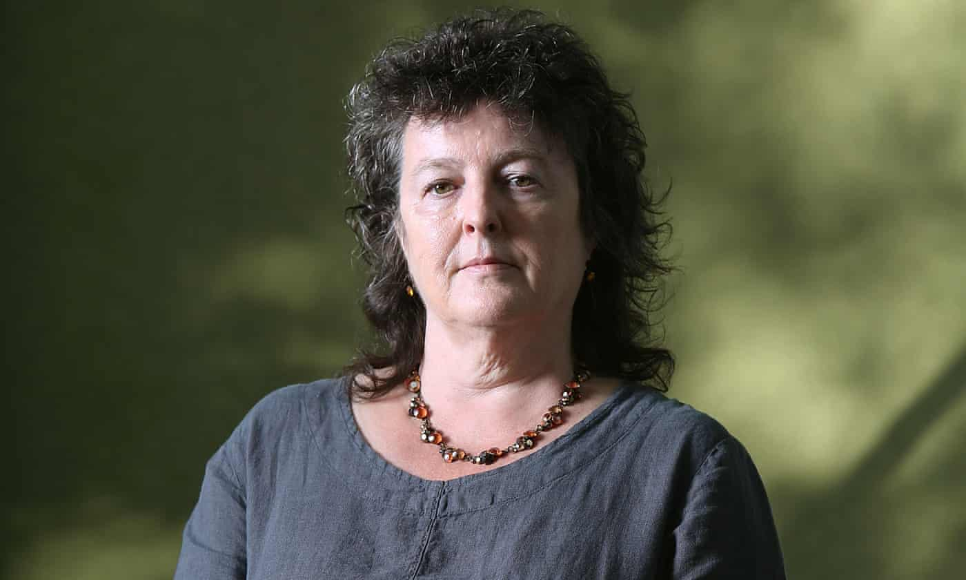 Poet Carol Ann Duffy is the centre of the photo standing infront of a blurred natural setting. She wears a grey top and chunky necklace with a stern facial expression