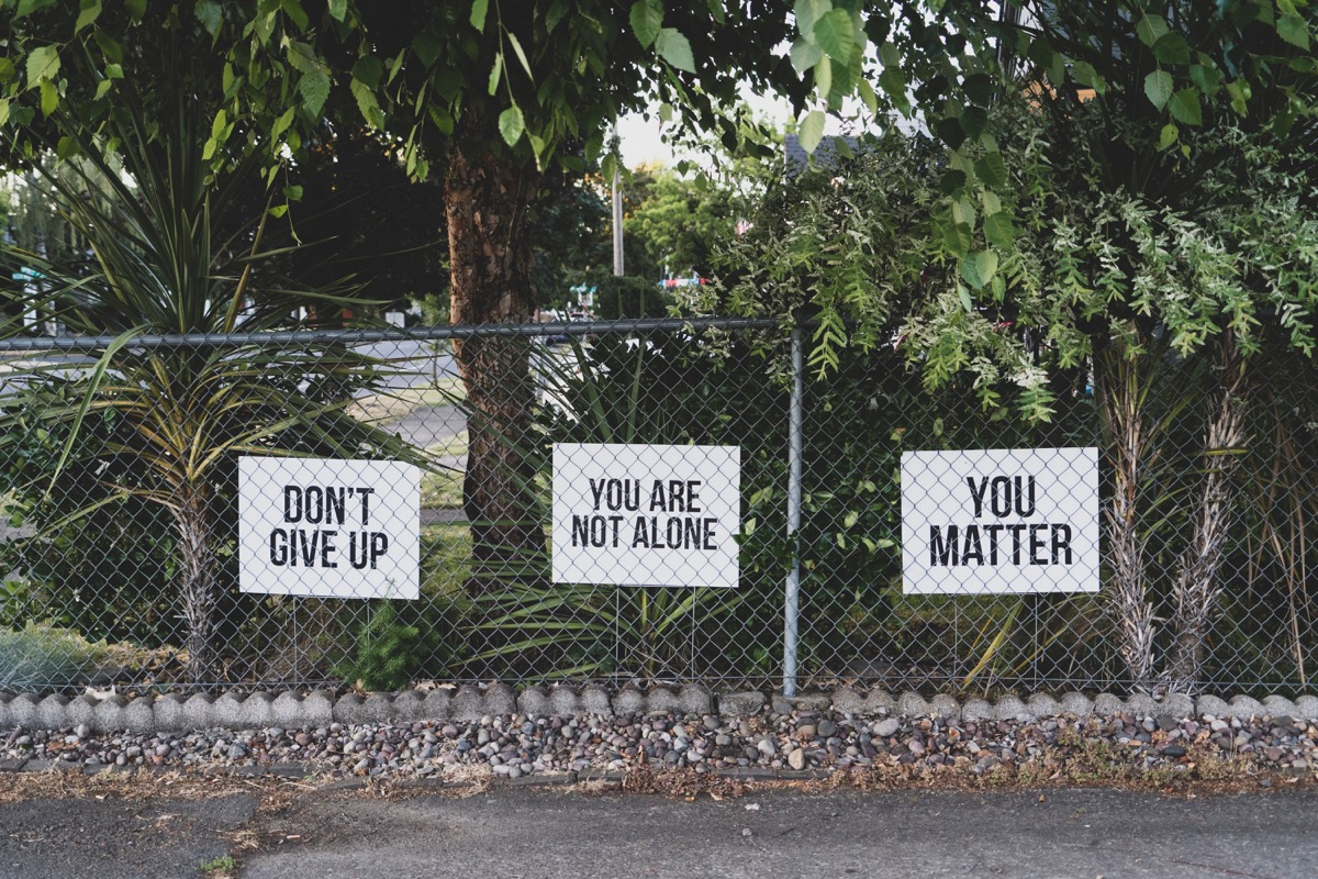 This image shows a fence, the fence has 3 signs on it. The signs say 'Don't give up' 'You are not alone' 'You matter'. Behind the gate are trees.