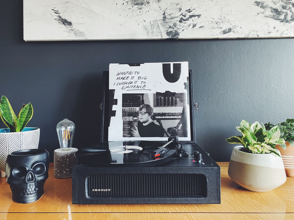 This image shows a vinyl player on a desk. The record that is playing is Ed Sheeran. There are also plants on the desk. The background wall is a deep blue colour.