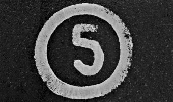 The image shows a number five encapsulated in a circle. It looks as though it has been painted to a road or a pavement.