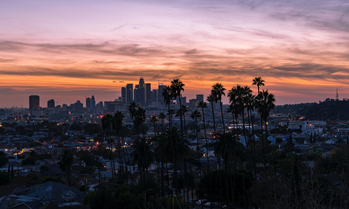 This image shows the Los Angeles skyline as it is approaching sunset. There is a silhouette of palm trees in the foreground, a view of the skyline and city in the middle ground and the sky in the background. The sky is a range of orange tones, suggesting that it is approaching night-time.