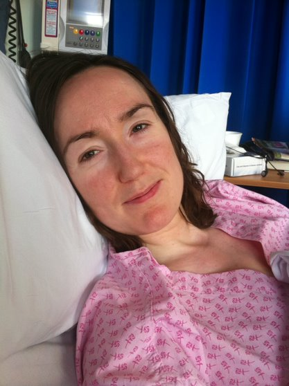 This portrait picture shows Louise as she lies in a hospital bed. She is wearing a pink hospital gown and smiles.