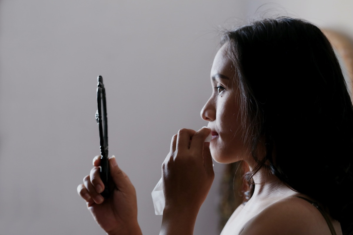 A lady wiping off her make-up whilst looking into a small black mirror. The lighting looks natural and is just lighting up the front features of her face.