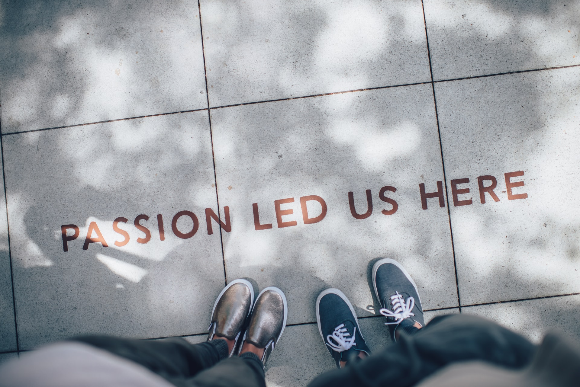 This is an image of two peoples feet, stood on a pavement. One of them is wearing golden shoes and the other is wearing blue shoes with white laces. There is a sign on the floor that reads 'Passion led us here.'