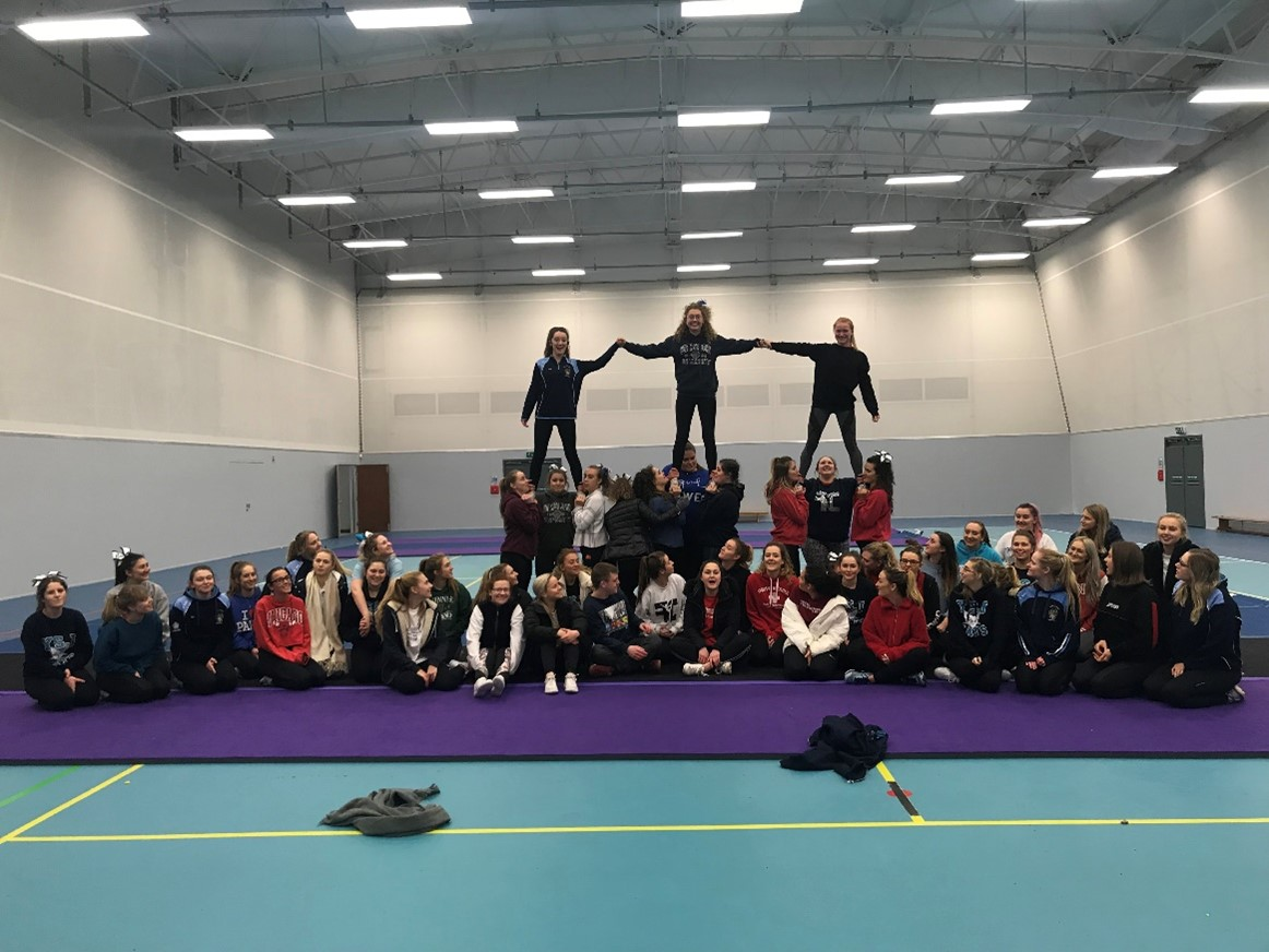 This picture was taken by Emma Bailey and shows a cheerleading team with 3 people standing on the shoulders and hands of others as they perform. The cheer team is static and seems to be in a gymnasium.