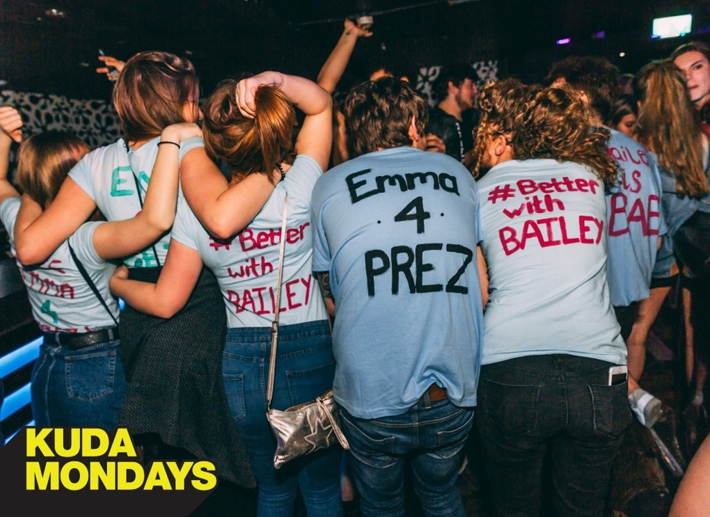 This picture is taken in the club and shows a group of friends wearing tops saying 'better with bailey' or 'emma for president' as her friends use her slogans to promote her campaign.