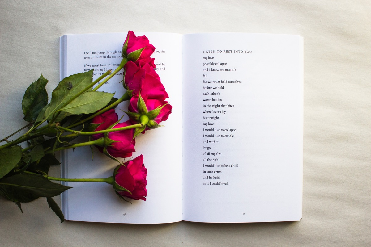 This image shows an open poetry book. The background appears to be plain - cream coloured. There are a bunch of red roses scattered across the left page of the book.