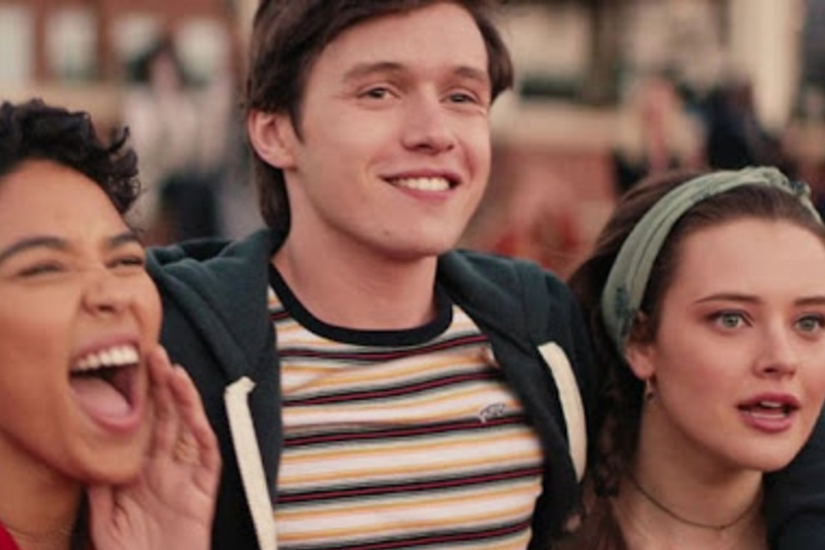 Simon, the main character, has his arms around two girls. Simon appears to have a smile on his face whilst the girl to his left looks at something in amused shock. The girl to his right is excitedly cheering for something.