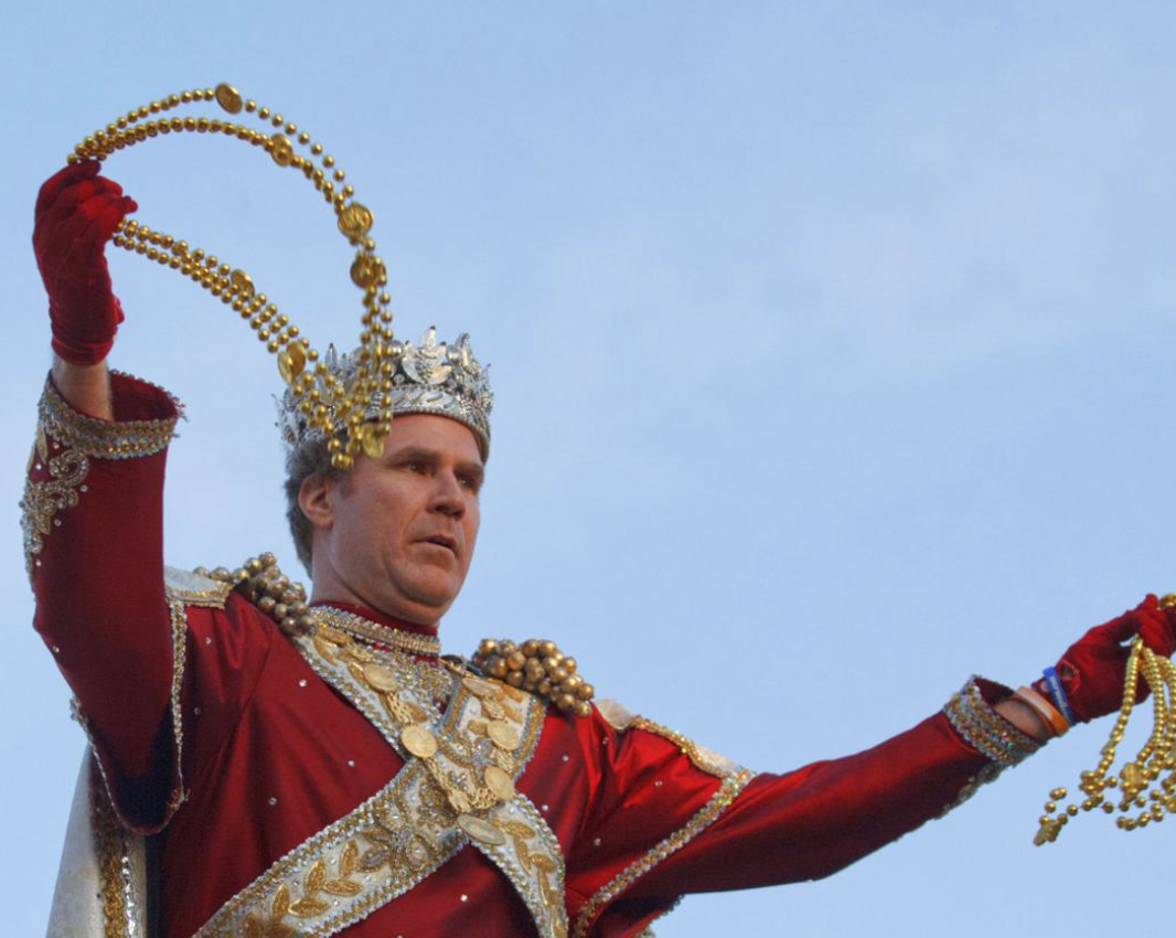This image shows Will Ferrel stood holding gold beaded necklaces. He is wearing a red outfit, coated in gold jewellery. He is also wearing a crown.