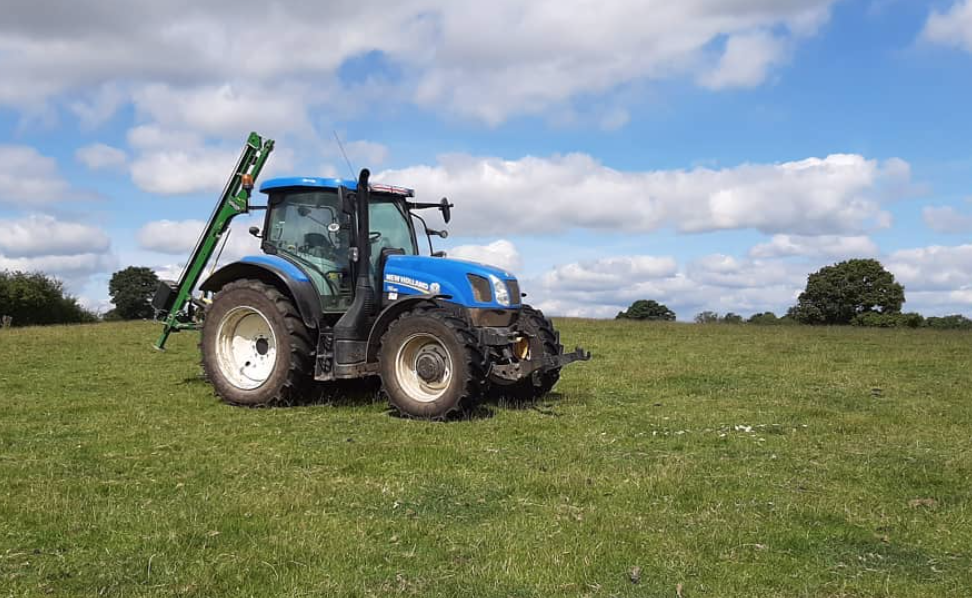 This image shows a blue tractor in the middle of a field. The sky is blue but cloudy.