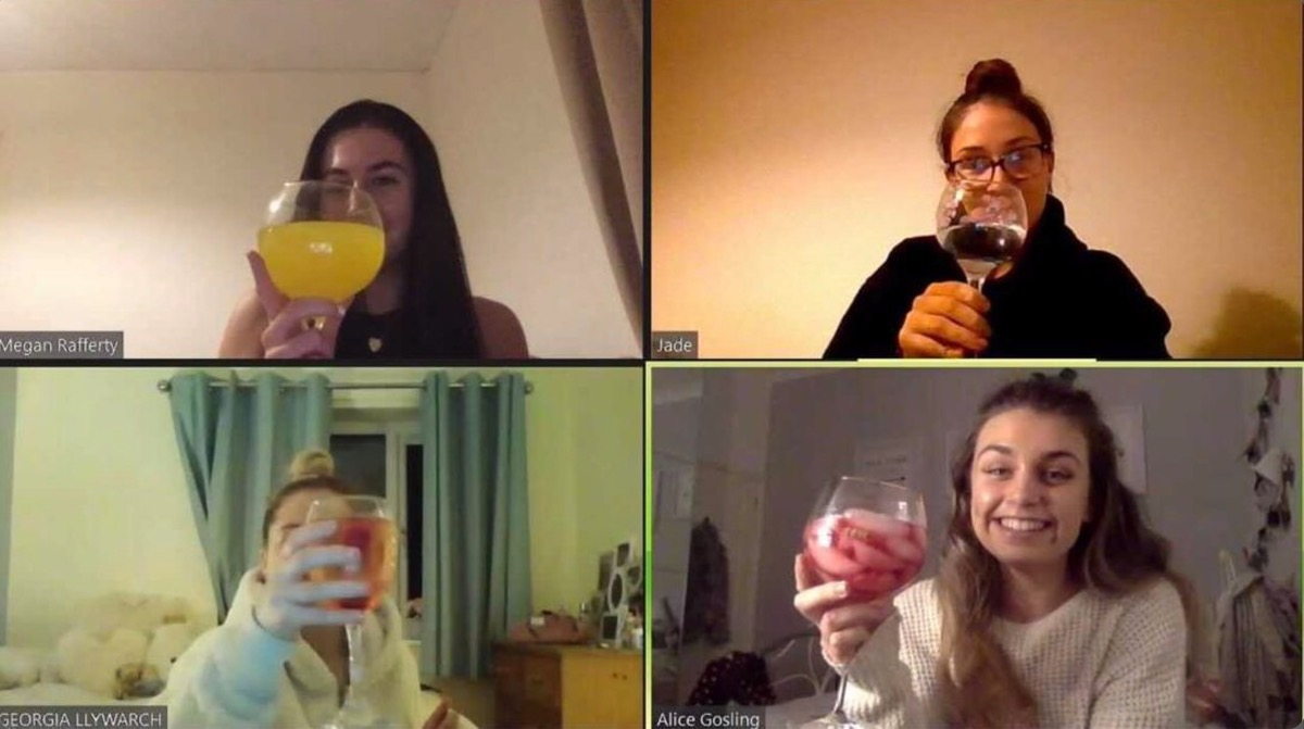 This image shows four girls on a zoom call. They are all holding up glasses of gin to the camera.