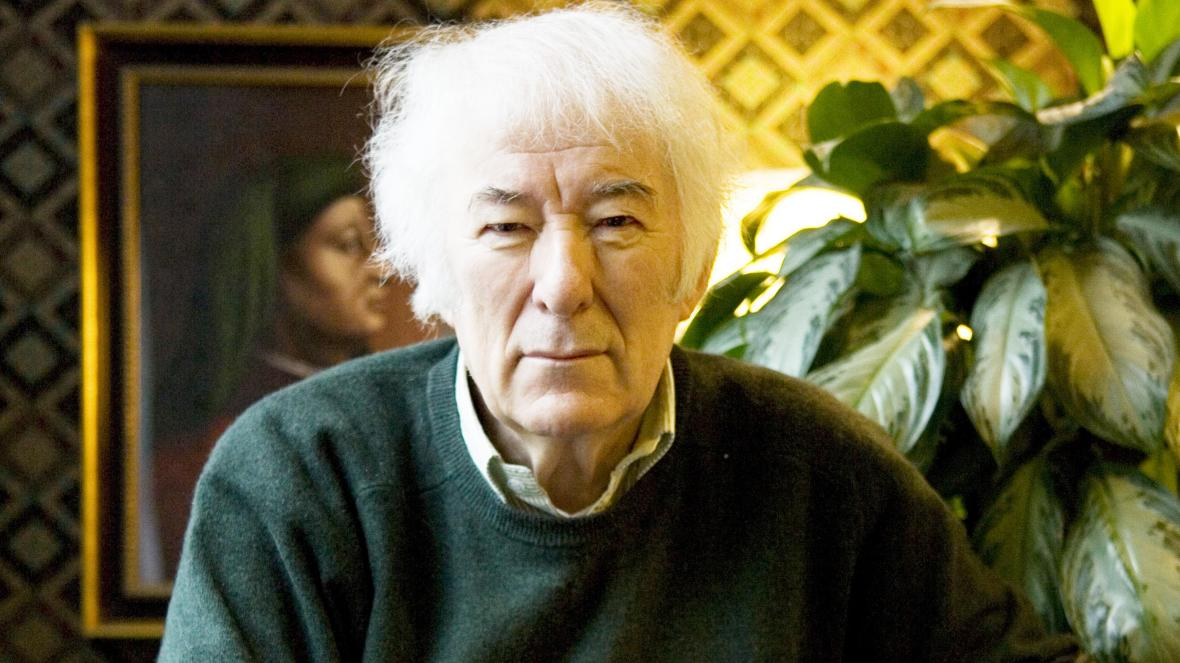 Seamus Heaney, photographed in 2008 infront of a large plant and a portrait painting. He has a very straight face and wears a green jumper with a shirt underneath