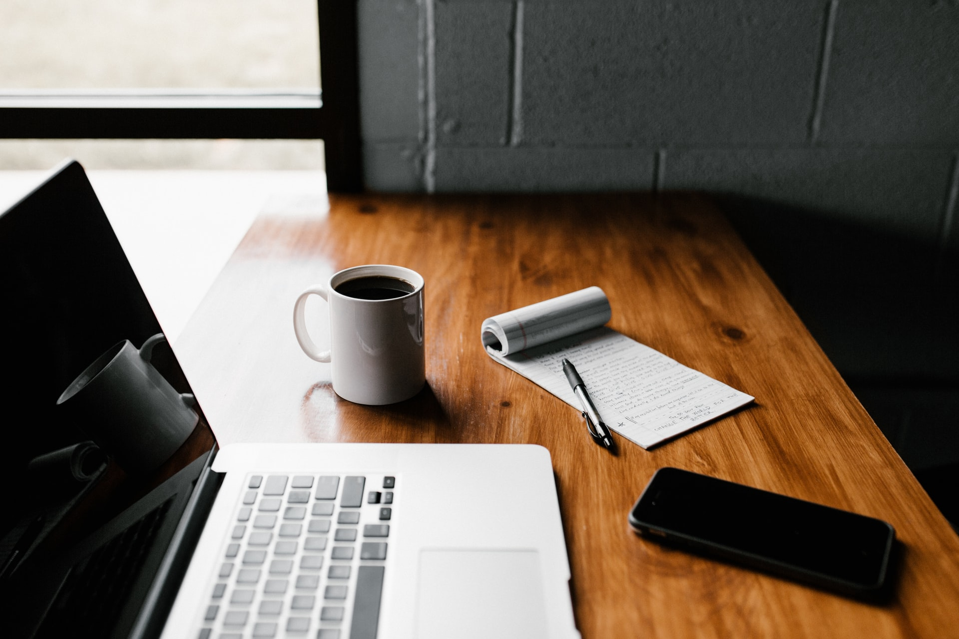 This image shows a wooden desk. On the top of the desk, there is a pen and paper, a mobile phone, laptop and a cup of coffee.