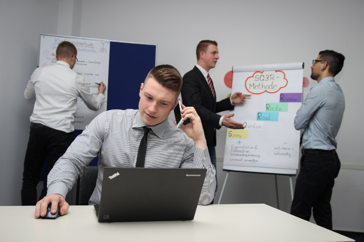 With three men in the background in suits standing around a very official looking white board, a man sits in shirt and tie in the foreground, head in hands whilst at his laptop.