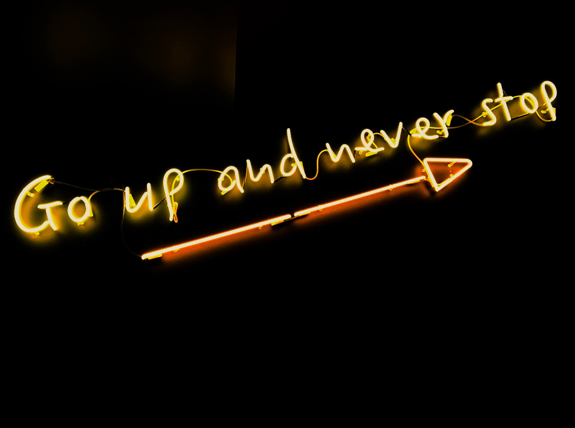 The image shows a neon sign on a black background. The neon sign reads 'Go up and never stop' and underneath has a neon arrow pointing North-east.