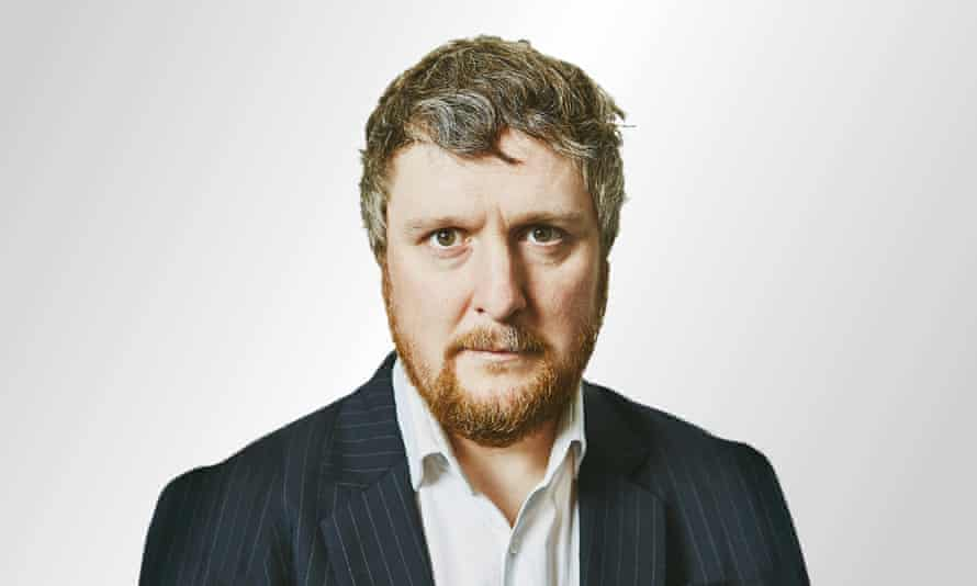 Tim Key photographed in a bright white studio setting with a stern face, a suit jacket and shirt with the top button undone.
