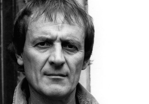A black and white photograph of poet, Tony Harrison with a straight face and white natural background.