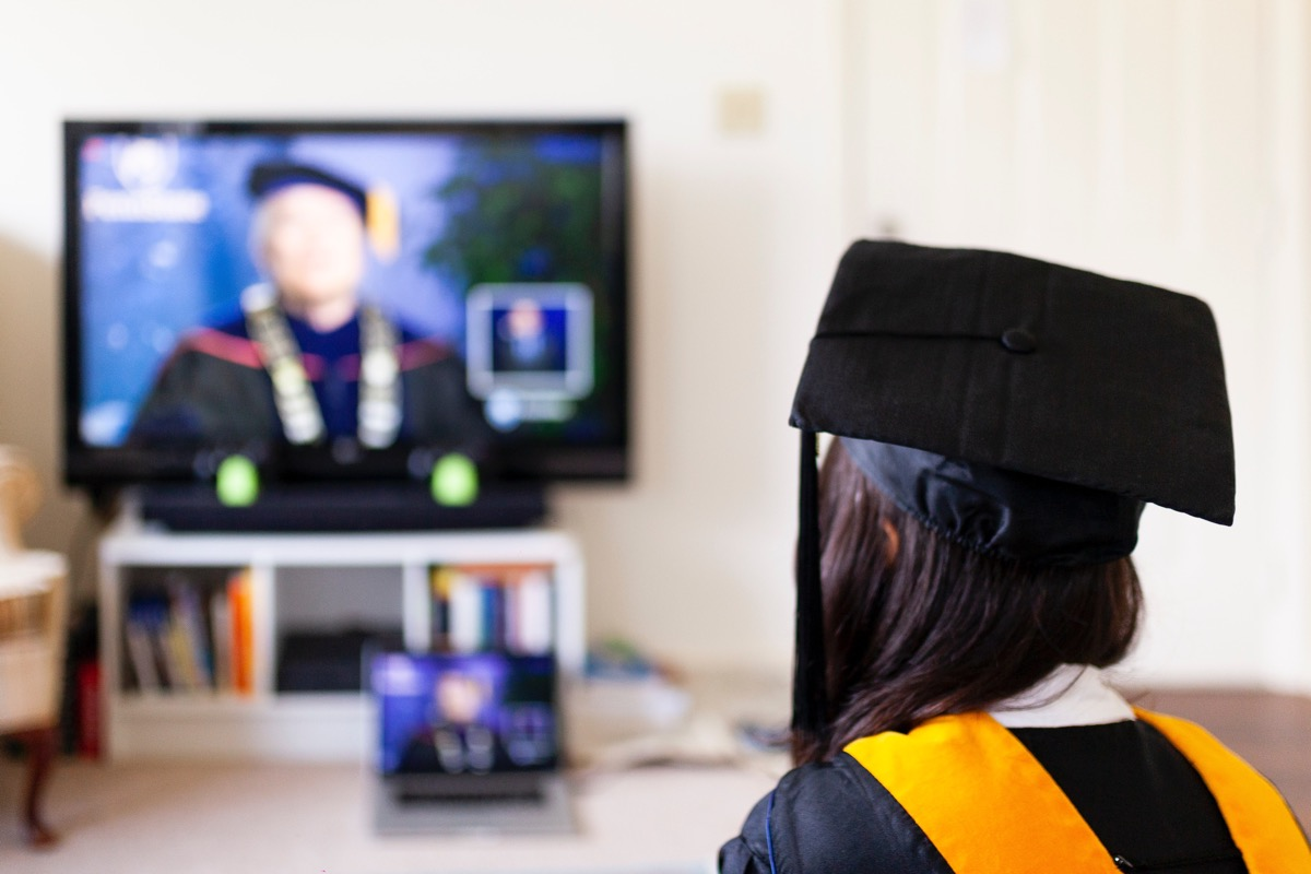 This image shows a girl sat in her university graduation cap and gown. She is in focus. The background of the image is not in focus but appears to be showing a TV screen.