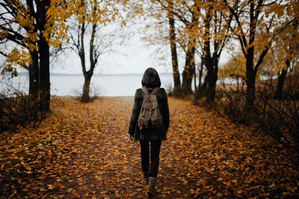 This image shows a woman walking through some woods. The leaves are brown and have fallen across the floor, suggesting that it is in the midst of Autumn. The woman is wearing a coat, boots and a backpack.