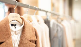 This image shows a clothes rack. The focus of the image is on a white shirt and brown coat, they are hung on a hanger. The other contents of the rail appear to be muted tones but that part of the image is un-focused.