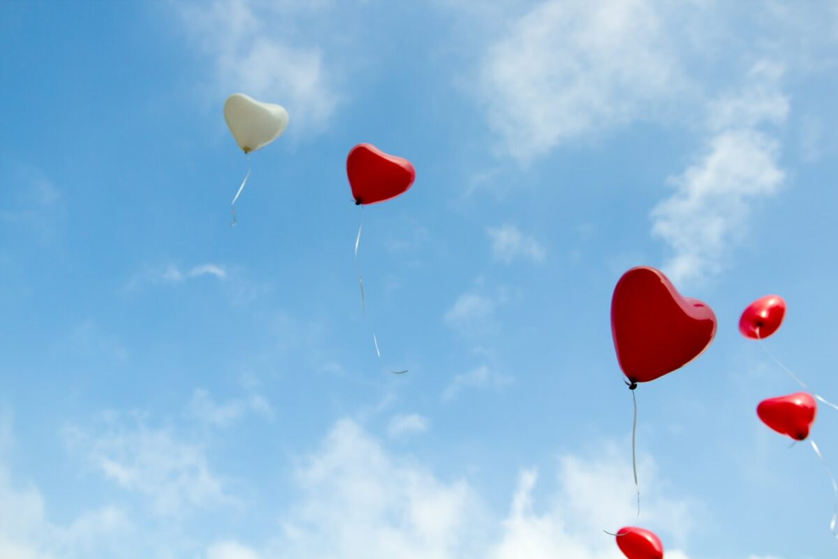 This picture is angled up towards the sky showing blue skies and white clouds. It looks like a nice day. In the sky, four heart shaped balloons fly away, one being white, and three being red.