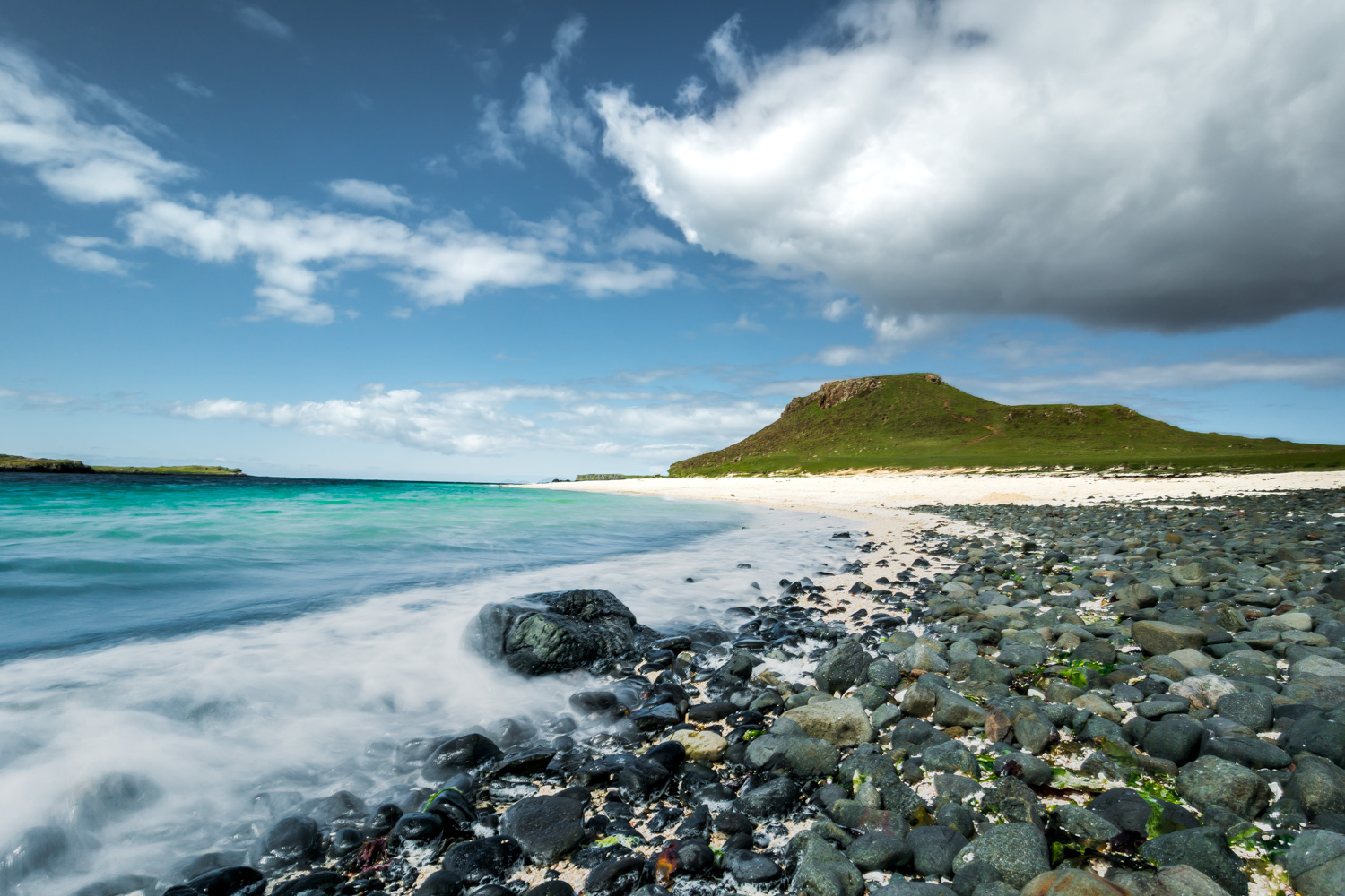 Coral Beach on the Isle of Skye is pictured here from a low angle. The sea is clear and turqoise toned with a beautiful green cliff pictured in the background.