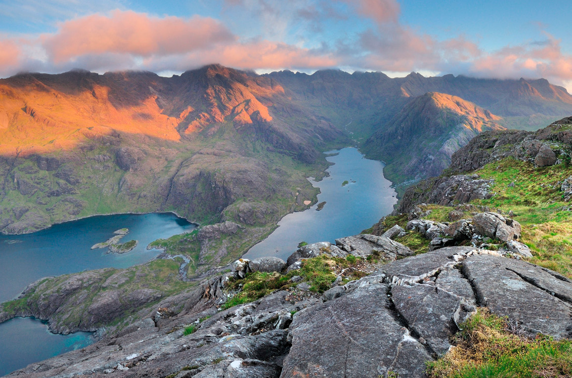 Loch Coruisk is pictured here from a birds eye view. The clouds are low with the harsh sun reflecting on the moutain tops.