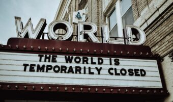 This image shows a cinema sign. The title of the sign says 'World' and the subtitle says 'The world is temporarily closed'.