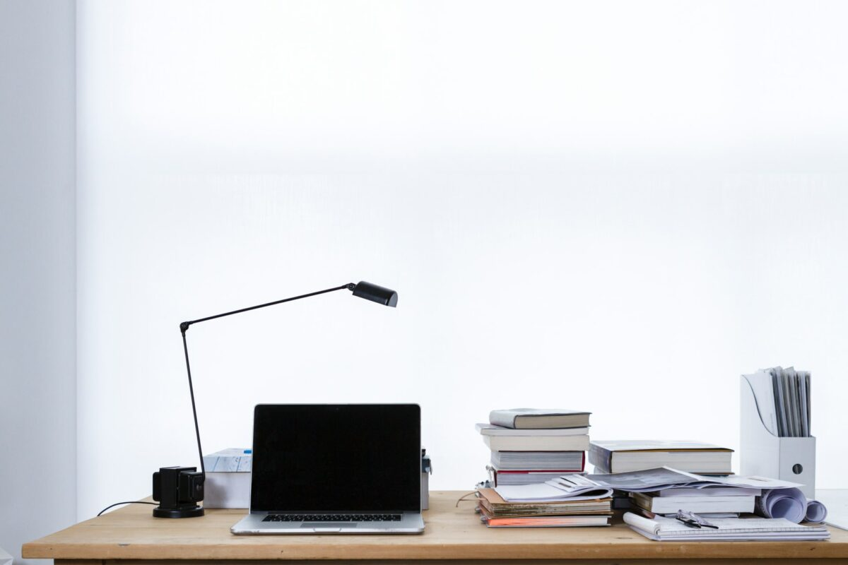 This image shows a desk with a laptop, books and a table lamp.
