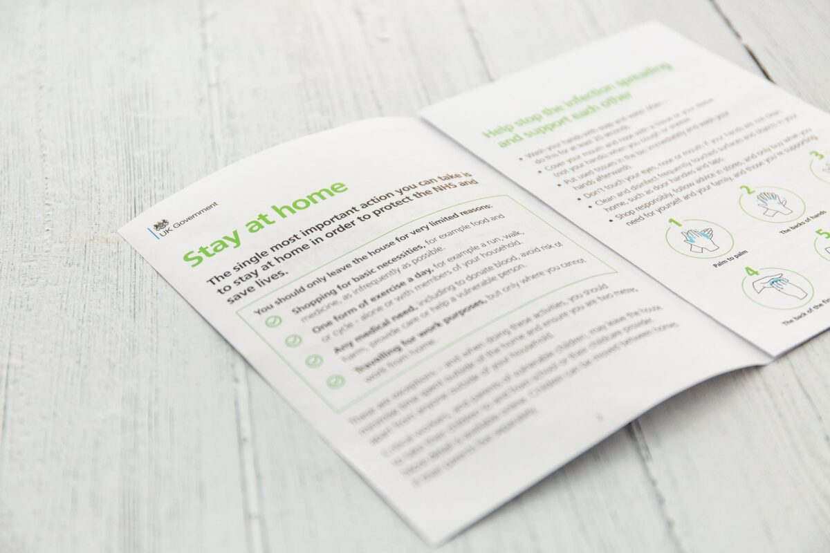 This image sees a COVID19 official leaflet reading 'stay at home' in large green font
