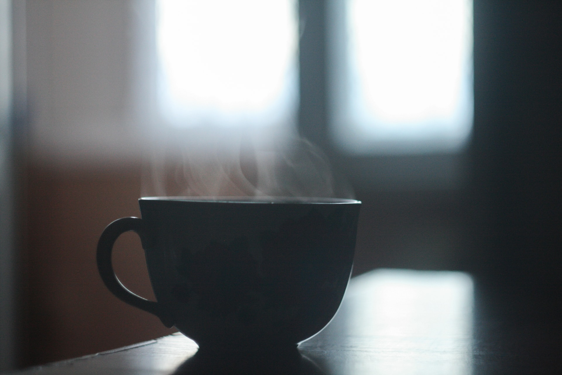 A dark image of a mug with steam rising in the foreground, brought to significance by the beaming light behind in the background.