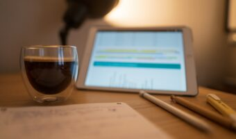 This image shows a wooden desk. In the foreground their is a notepad, filled with notes as well as some pens and pencils. In the middle-ground, there is an espresso coffee and an iPad. In the background, there is a lamp, shining.