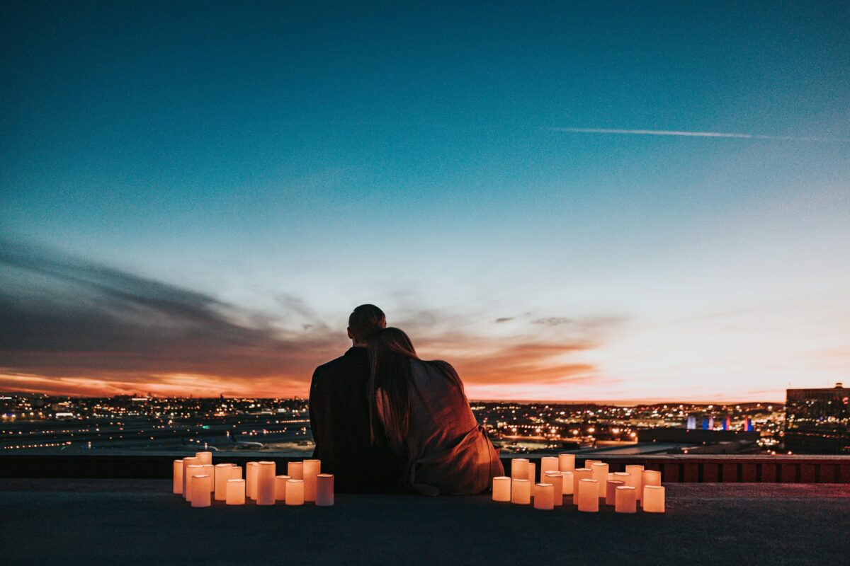 This image shows a couple sat admiring a view of a lit-up city. The sun is nearly set and they are surrounded by candles.