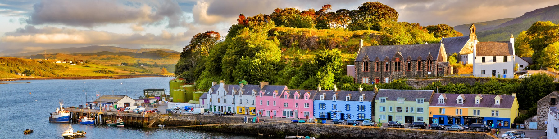 Portree, The isle of skye sees multicoloured homes on the seafront with high green mountains in the background.