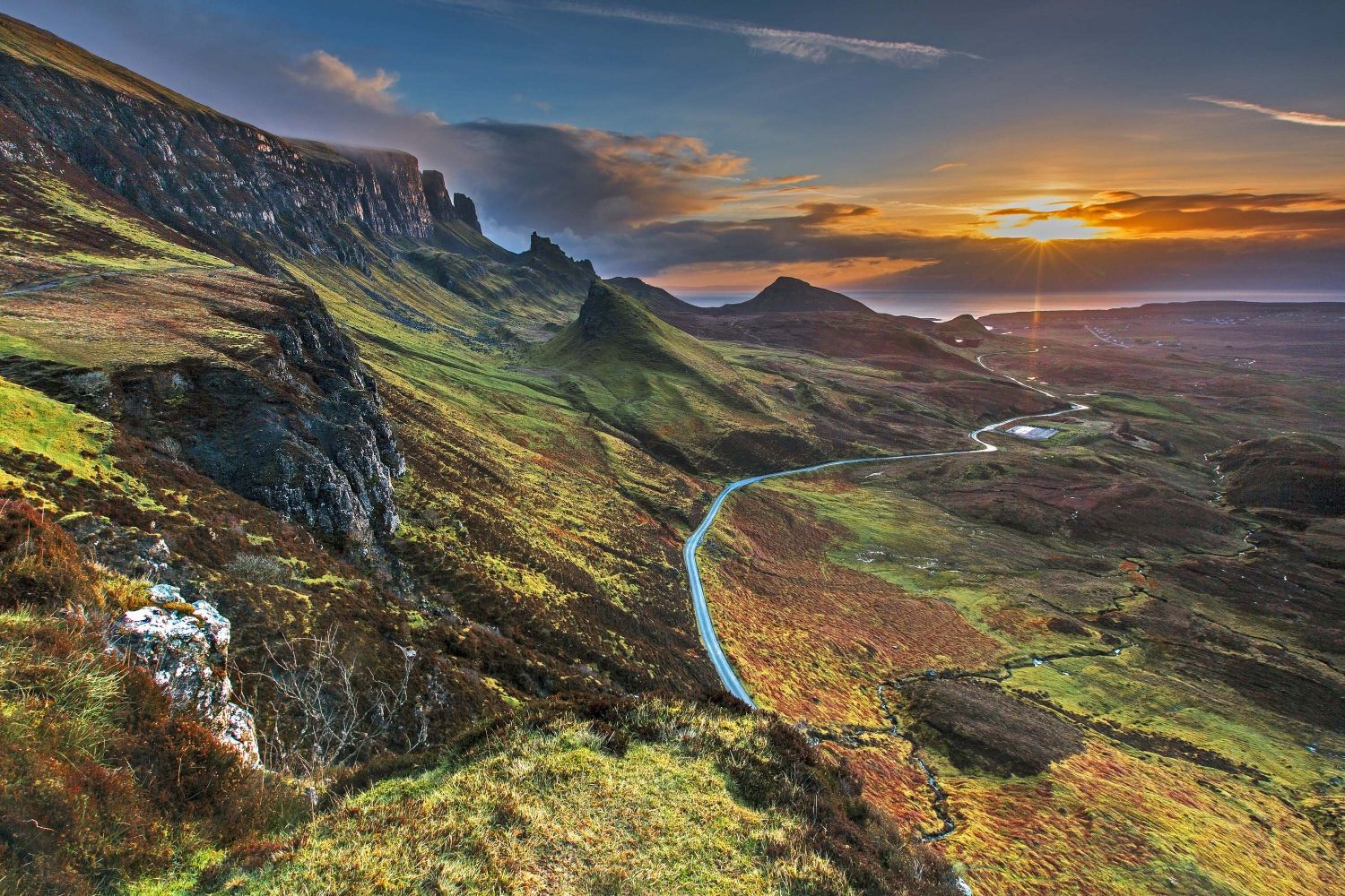 This image shows the sunrise of the Quiraing, Scotland. The sunset is blue and orange toned