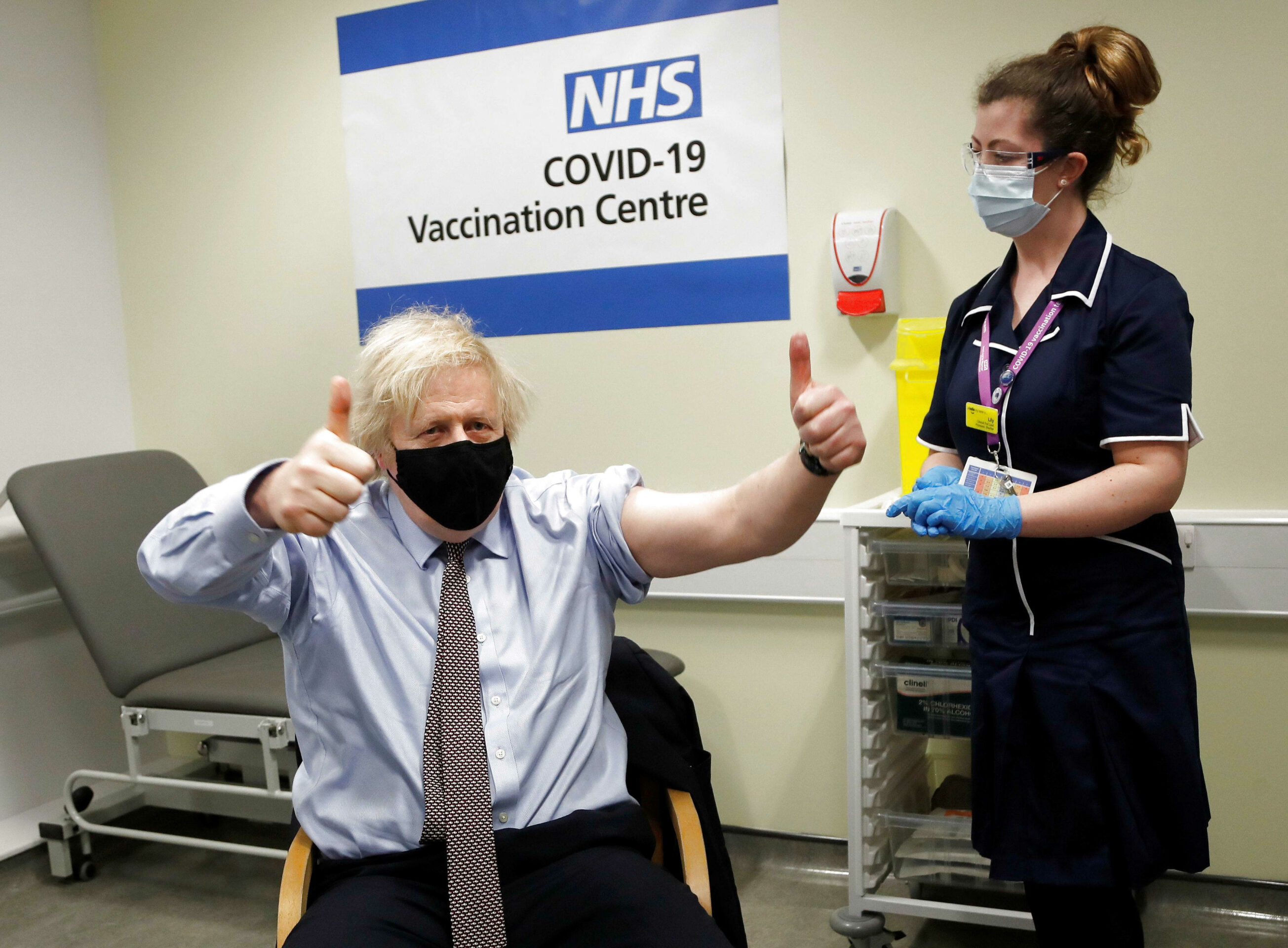 This image shows Boris Johnson in a vaccination centre with his hands in the air and thumbs up wearing a black mask. He had just received his first dose of his AstraZeneca vaccine.