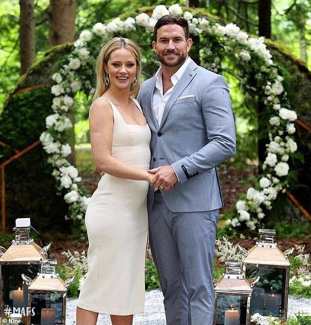 MAFS stars Jessika Power and Dan Webb are pictured here on the final episode of season 6. Dan Webb wears a grey suit and Jessika Power wears a white/cream midi-dress.