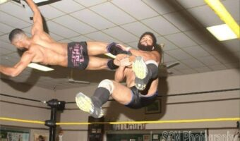 Two wrestlers are pictured here mid-air.