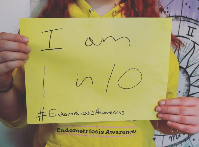 This image shows Natalie holding a sign saying 'I am 1 in 10 #endometriosisawareness'