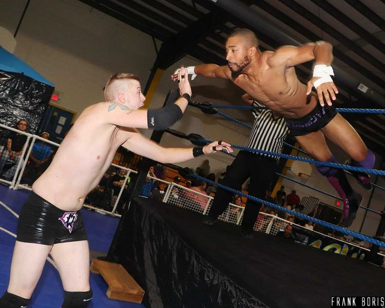 This image shows two wrestlers, one being JT Funk who is jumping mid-air as this photo has been taken.