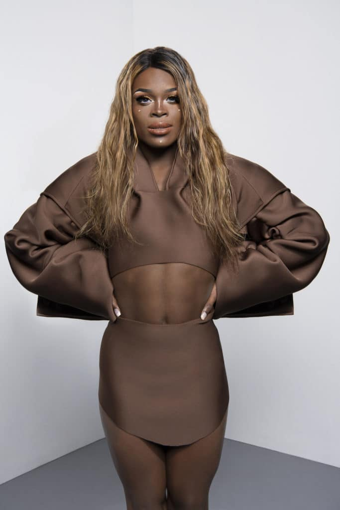 Drag Race UK star Asttina Mandella is stood here with a brown co-ord on  and a mid-length brown wig.