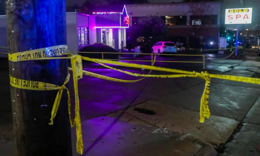 The crime scene is pictured here with yellow caution tape. Blue lights reflect off of the buildings.