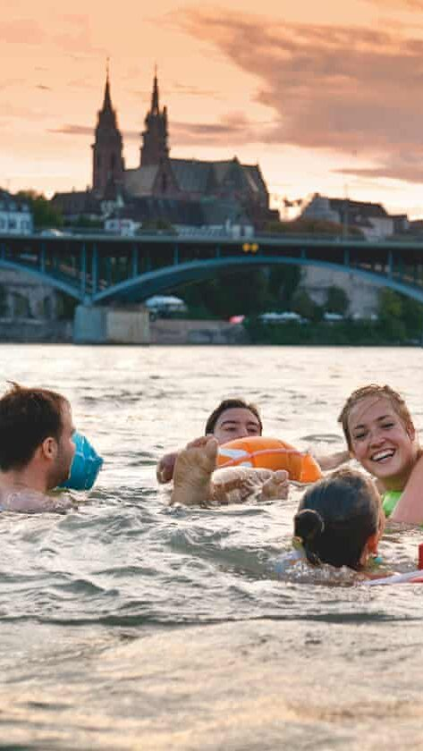 A family are seen swimming in the River Rhine with Basel old town visible in the background