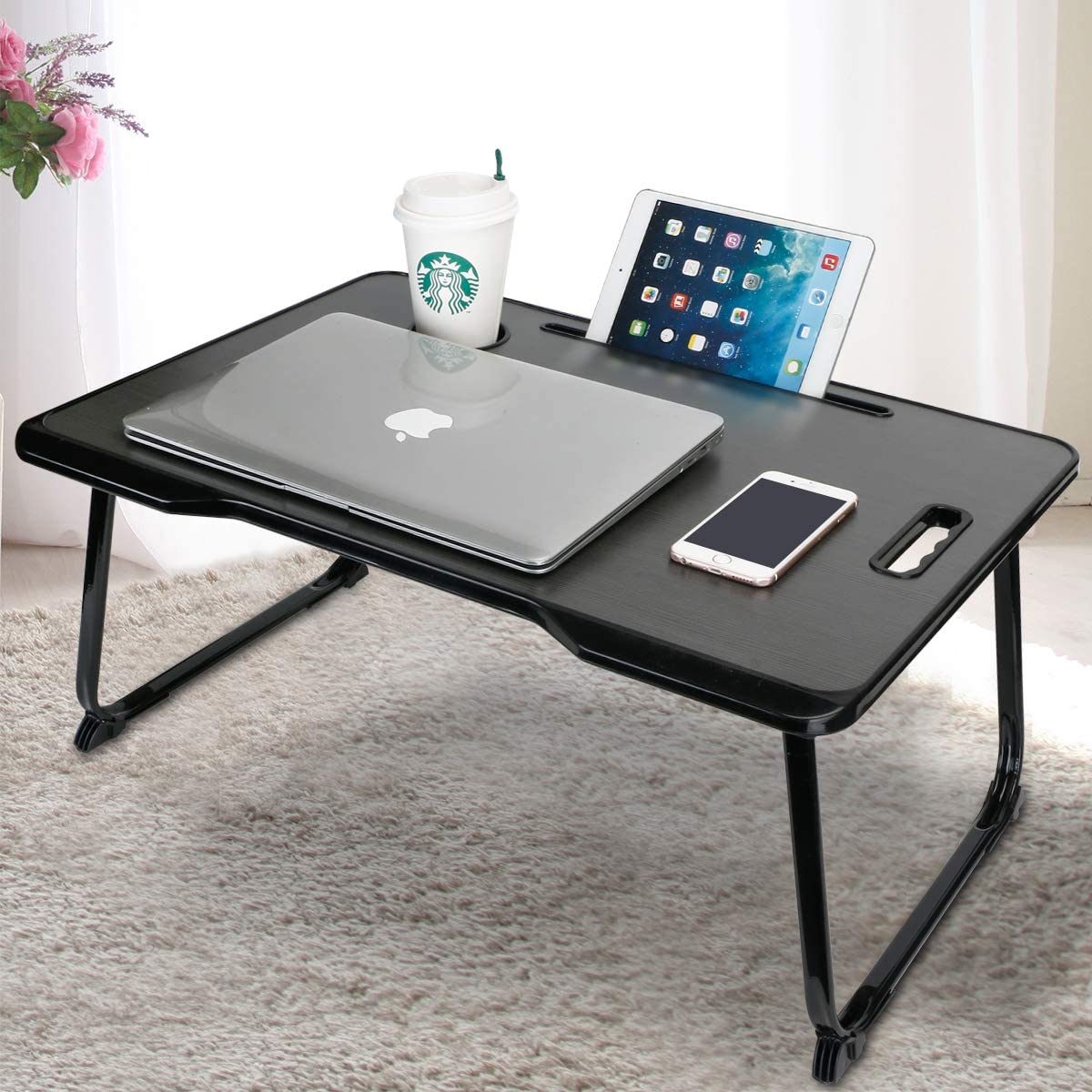 This image shows a laptop table for your bed with a MAC book, iphone, ipad and starbucks cup on top.